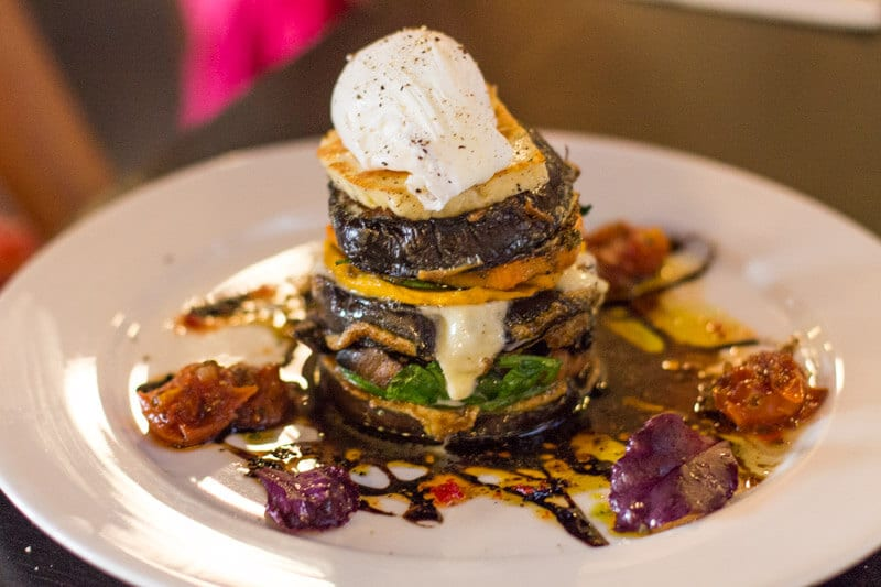 veggie stack of Grilled eggplant, pesto, buffalo mozzarella, spicy tomato, sweet potato, pumpkin, spinach, mushroom and halloumi, topped with a poached egg at Fourth Child Restaurant in Ipwsich, Queensland