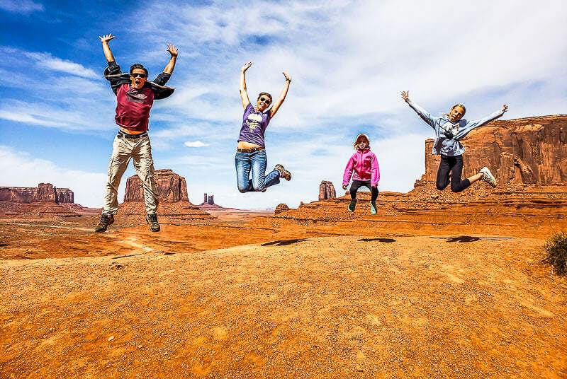 A family jumping in the air at Monument Valley Navajo Tribal Park