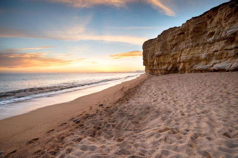 Sunset over the cliffs at Hive Beach at Burton Bradstock near Bridport on the Dorset coast