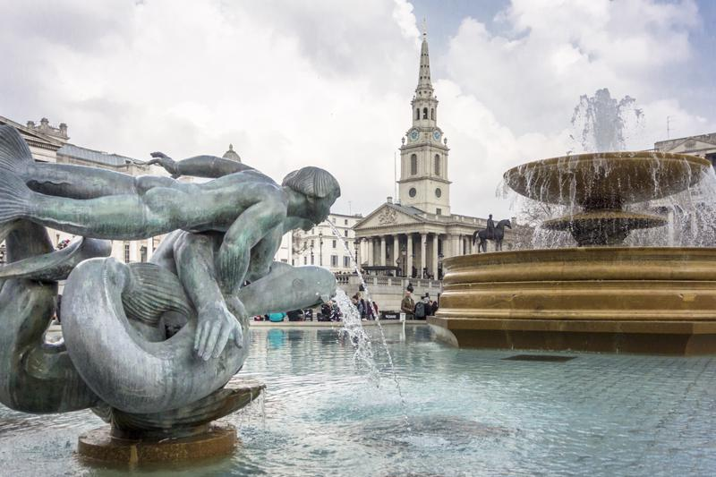 Statue of a mermaid with dolphins in the fountains of Trafalgar Square, with a statue of King George IV on his horse and St Martin in the Fields church in the background, London, UK