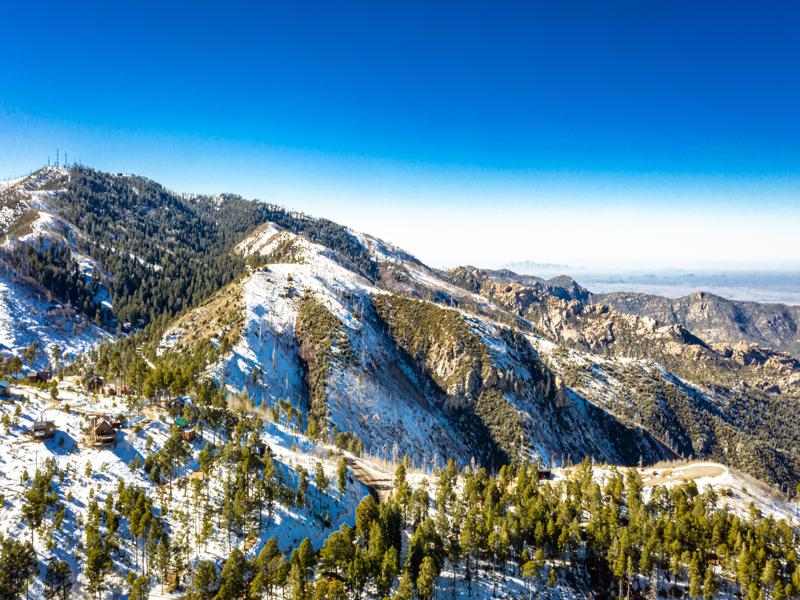 An aerial image of the summit of Mt. Lemmon outside of Tucson, Arizona covered in snow with a vibrant blue sky.